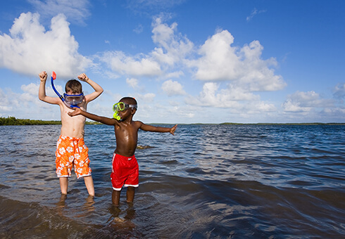 Two small boys playing with snorkel gear on a beach - one African American one Caucasian. John Pennecamp Park, Florida Keys.