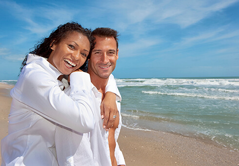 Happy couple in white shirts standing at beach