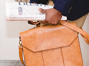 man holding briefcase and business section of newspaper