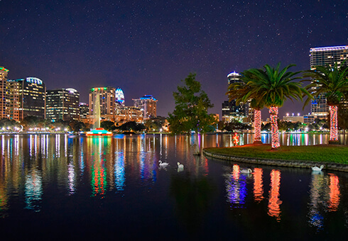 Orlando, Florida cityscape and skyscrapers with reflections of Lake Eola at night with palm trees, fountain and swans.