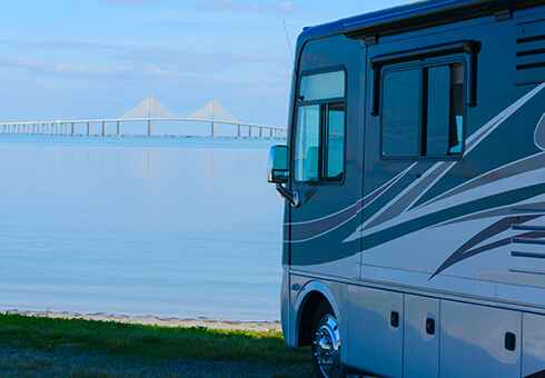RV recreational vehicle is parked at the beach overlooking Tampa Bay in Florida with the Skyway Bridge in the background