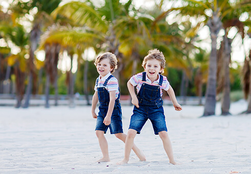 Two little kids boys having fun on tropical beach, happy best friends playing, friendship concept. Siblings brothers, twins in family look with palms on background