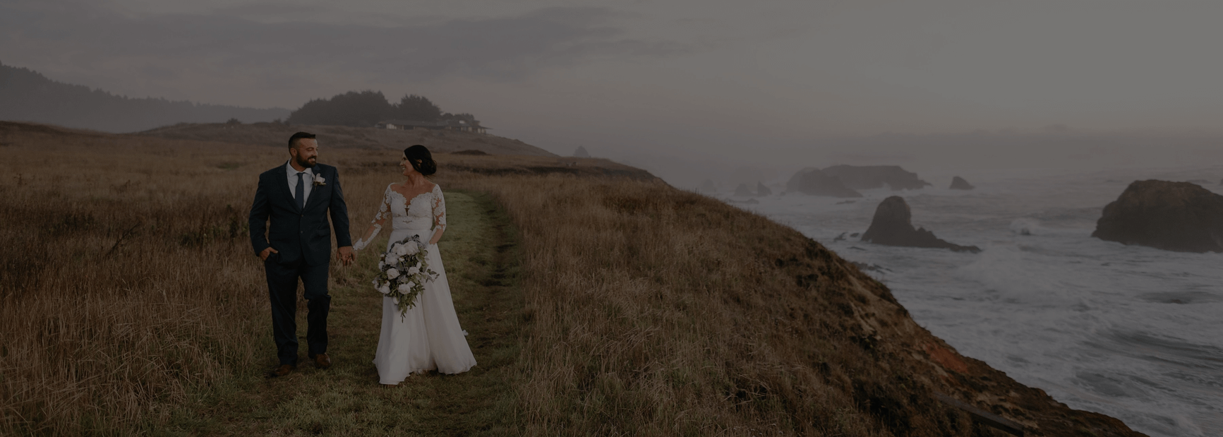 Photo of just married couple walking along coastal path